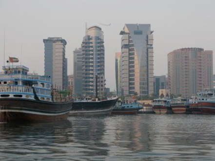 Aircraft between buildings behind dhows on Dubai Creek