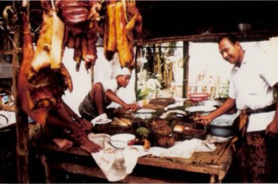 Bali village wedding feast preparation with hanging pork