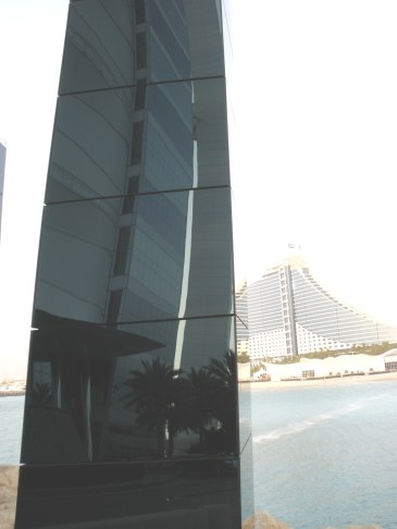 Curve of Burj Al Arab reflected against background of Al Jumeirah Beach Hotel Dubai