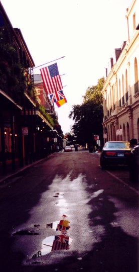 Flags reflected in puddle in the French Quarter New Orleans