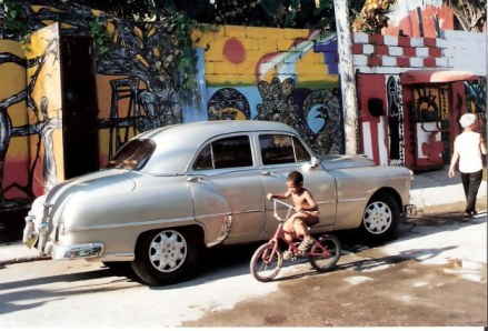Havana-Classic-car-against-mural-covered-walls-in-Barrrio-Cayo-Hueso