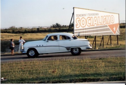 Havana-classic-car-by-revolution-sign