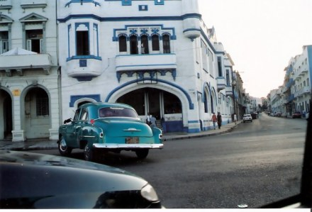 Havana-classic-cars-in-front-of-colourful-building-Habana-Centro