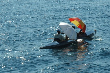 Kayak paddlers with umbrellas