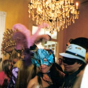 Masked revelers at French Quarter balcony party during New Orleans Mardi Gras