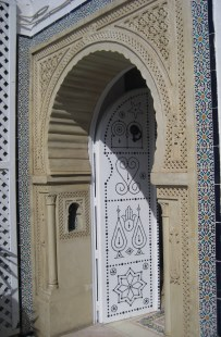 Mosaics, carvings, and black studded door in entrance in Hammamet, Tunisia