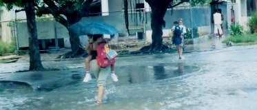 Mothers carrying children above flooded streets in Havana