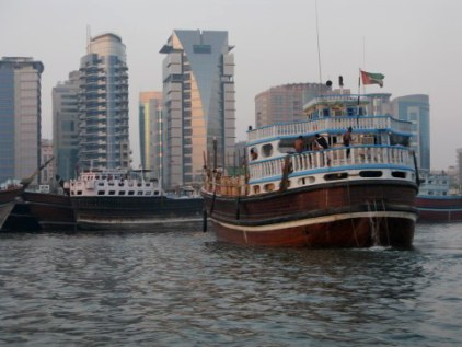 Traditional wooden trading dhow pumping bilge - Dubai Creek