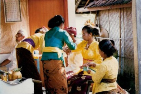 Tying bride and groom with cords at Bali village wedding