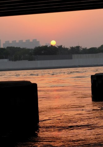 Under-bridge sunset outlines Dubai Creek