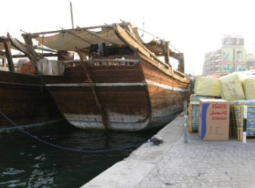Wooden dhow traders with goods on dock Dubai Creek