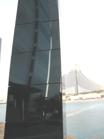 Curve of Burj Al Arab reflected against background of Al Jumeirah Beach Hotel Dubai