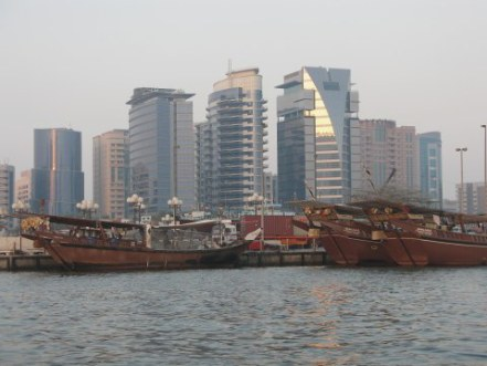 Deira skyscrapers and dhows with sunset water on Dubai Creek