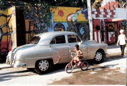 Havana-Classic-car-against-mural-covered-walls-in-Barrrio-Cayo-Hueso