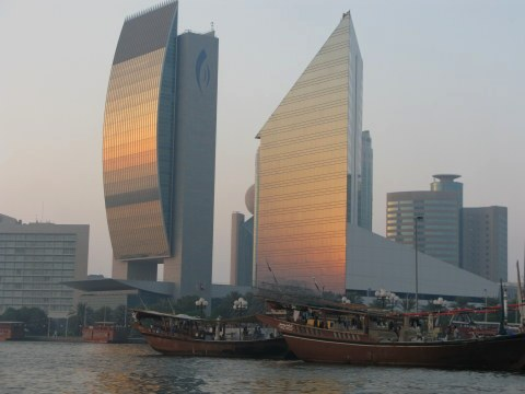 National Bank of Dubai and Chamber of Commerce Buildings  with wooden ships on Dubai Creek