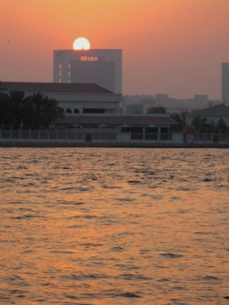 Sun setting behind arched building on Dubai Creek